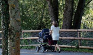 Frau spaziert mit Buggy