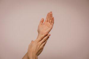Hände die einen Skin Scrubber verwenden